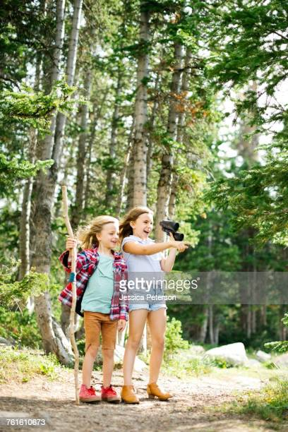 Girl (8-9) and boy (6-7) standing in forest