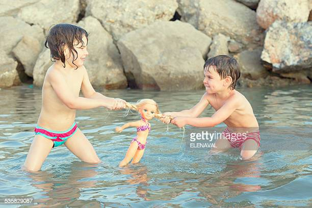 Girl and boy standing in lake fighting over doll