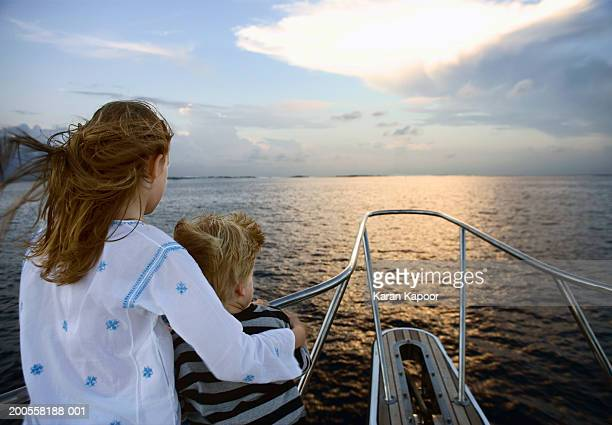 Girl and boy (4-9) standing on deck of boat, looking at view