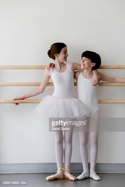 Girl and boy (12-14) standing together in ballet class, smiling