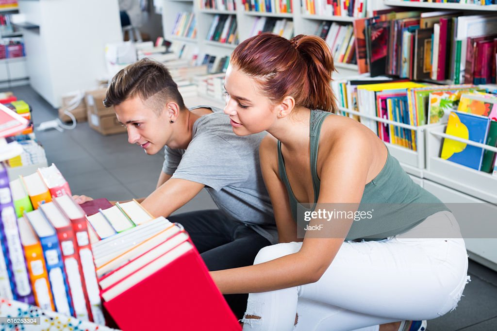 girl and boy teenagers in book store : Foto de stock