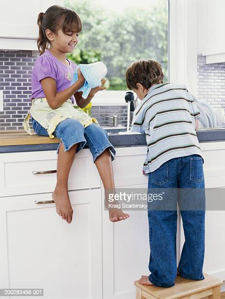 Girl and boy (5-7) washing and drying dishes in kitchen