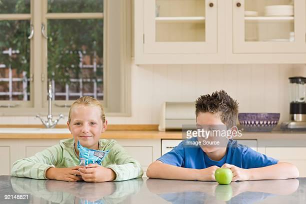 Mädchen und junge mit Chips und apple