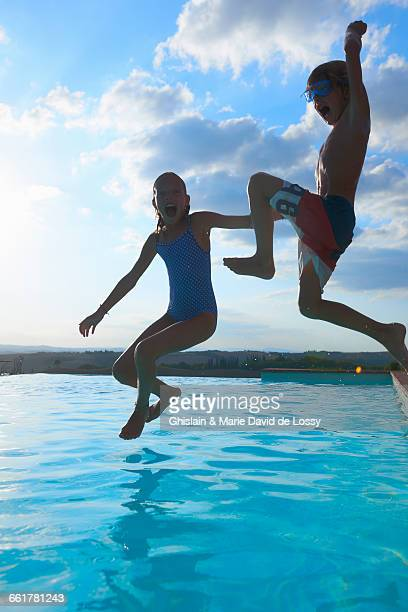Girl and brother jumping into swimming pool, Buonconvento, Tuscany, Italy