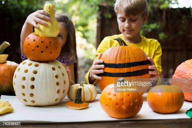 Girl and brother stacking carved pumpkins on garden table