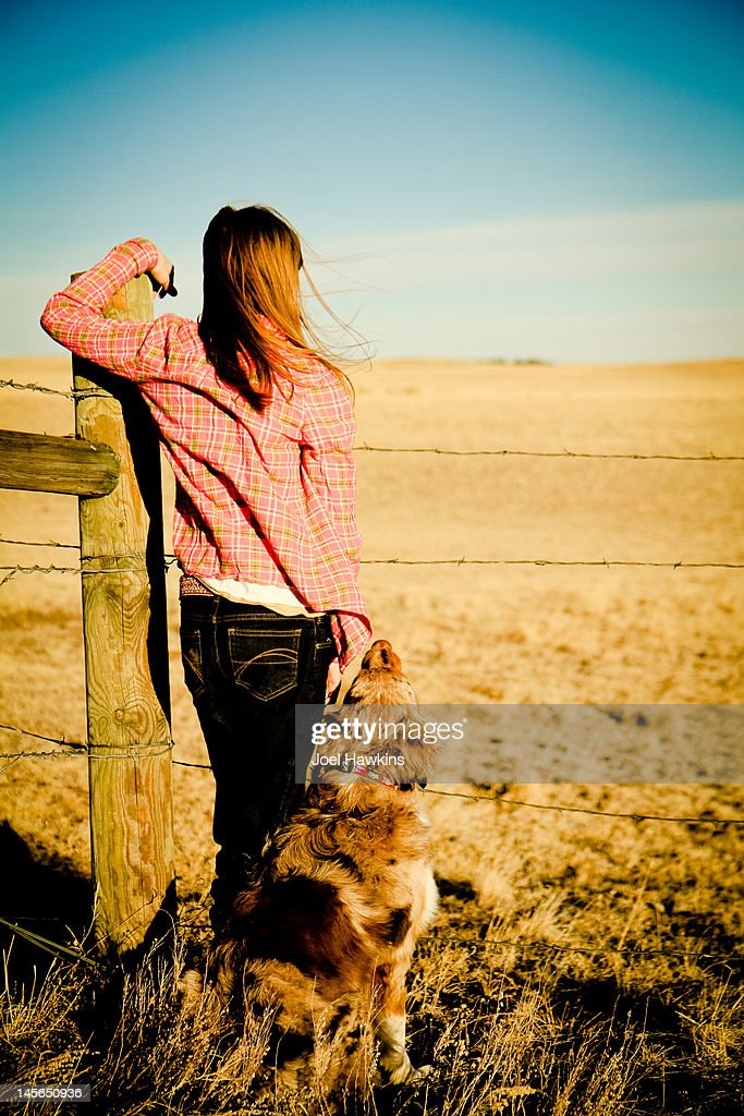 Girl and dog looking over fence : Stock Photo