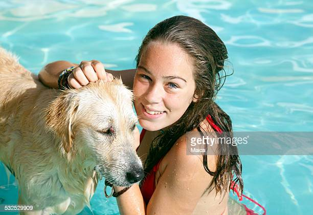Chica y perro jugando en la piscina