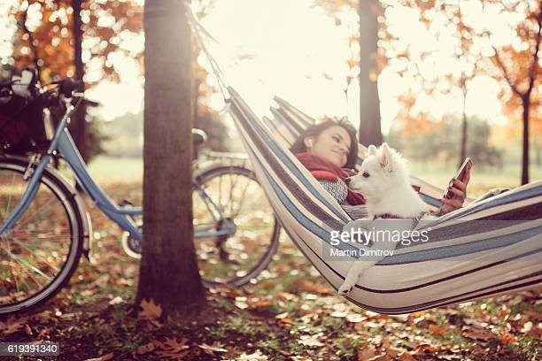 Girl and dog relaxing in hammock
