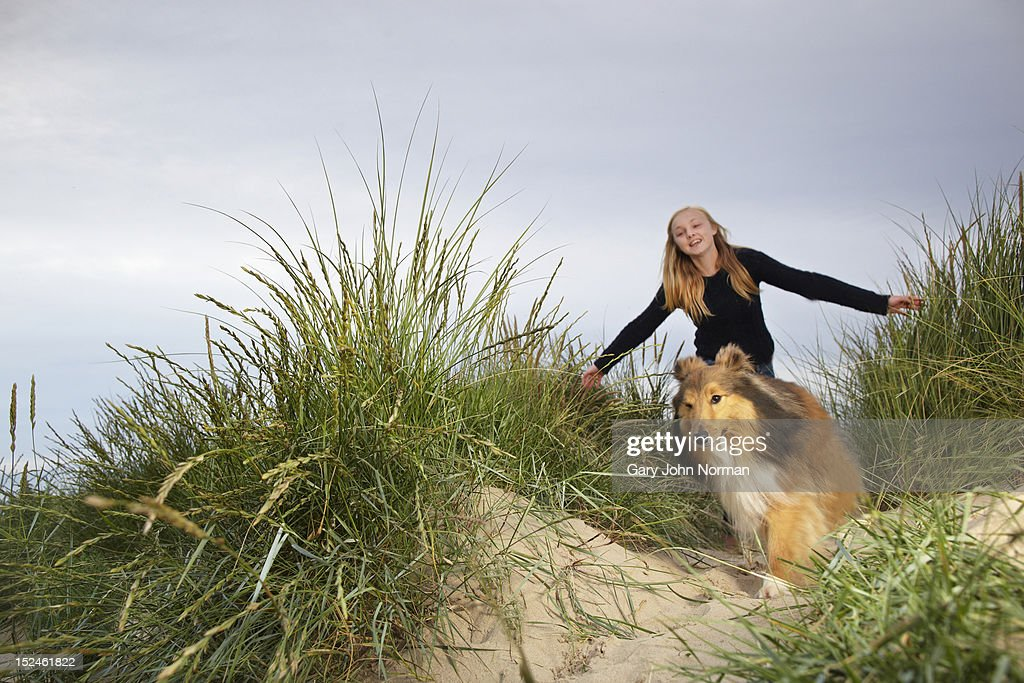 girl and dog running through sand dunes : Stock Photo