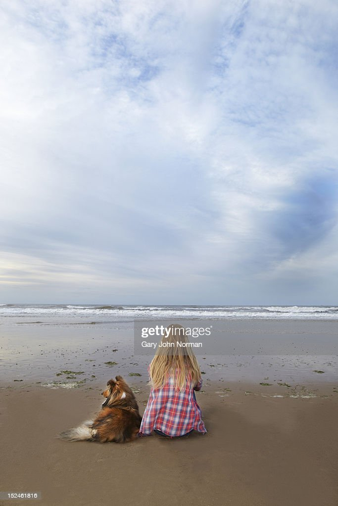 girl and dog sit on beach looking out to sea : Stock Photo