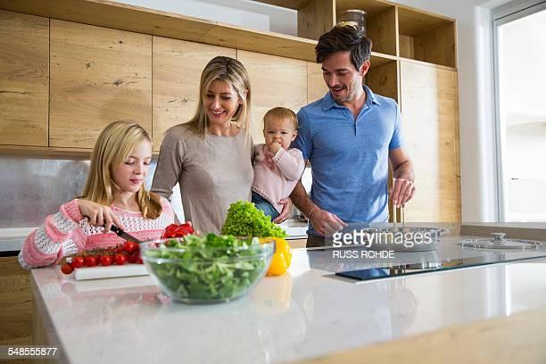 Girl and family preparing fresh vegetables in kitchen