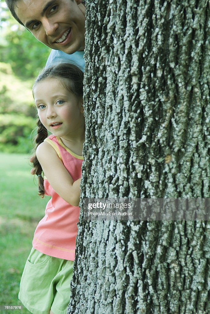 Girl and father peeking around tree trunk