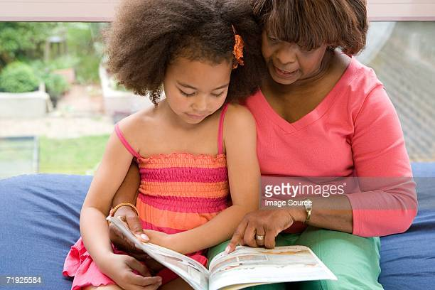 Girl and grandmother reading picture book
