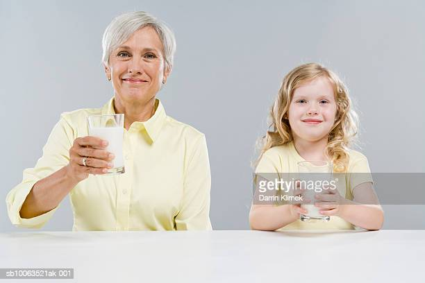 Girl (4-5) and grandmother sitting side by side holding glasses of milk, portrait
