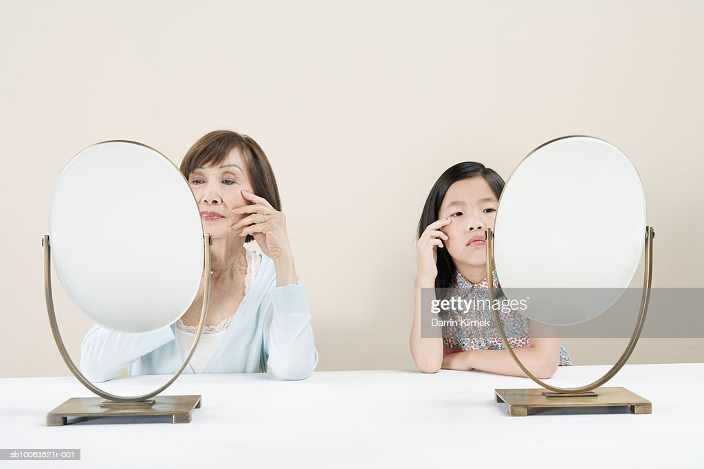 Girl (8-9) and grandmother sitting side by side looking at reflections in mirror : Stock Photo