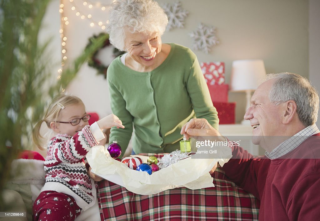 Girl and grandparents decorating for Christmas : Stock Photo
