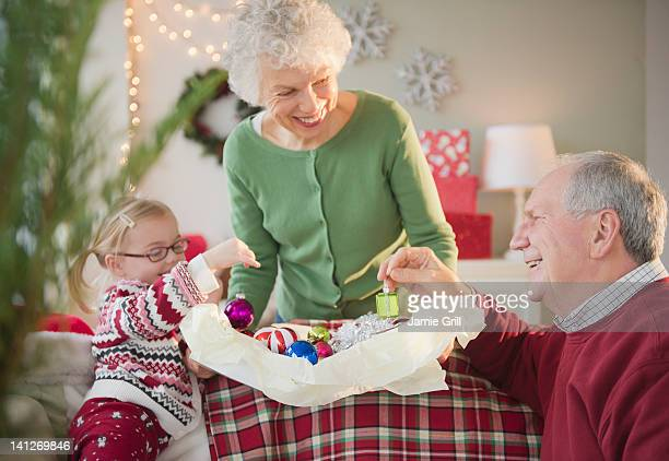 Girl and grandparents decorating for Christmas