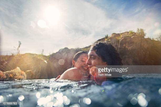 Girl and guy in water with sunlight