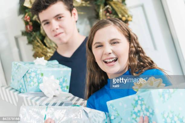 Girl and her brother carrying Christmas gifts