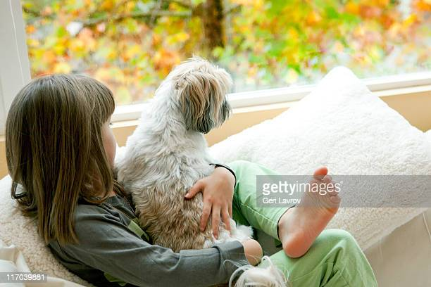 Girl and her dog looking out the window