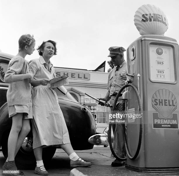 A girl and her mother hold a map and ask a question while a Shell gas station attendant fills up the tank of their automobile Virginia 1949