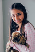 Portrait of a girl with her pet rabbit. She is holding it close to her and smiling at the camera.