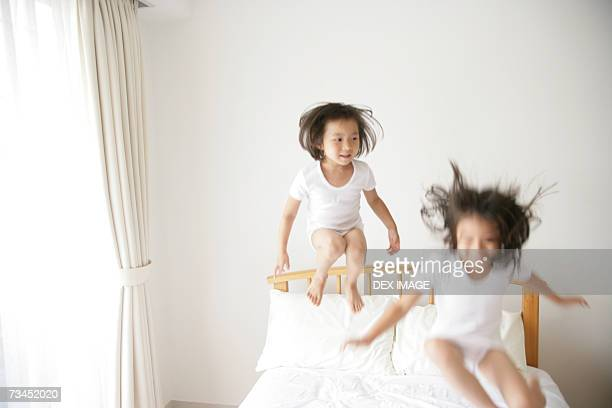 Girl and her sister jumping on the bed