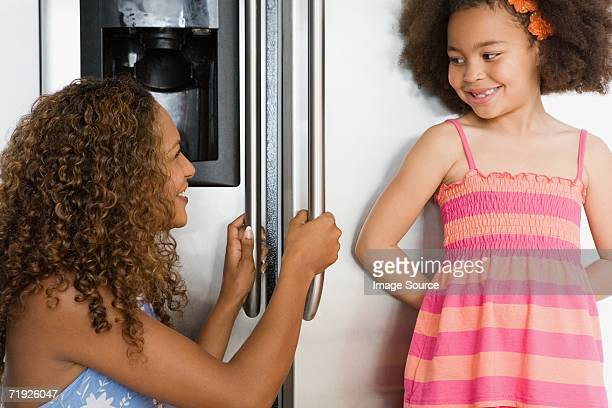 Girl and mother in front of refrigerator