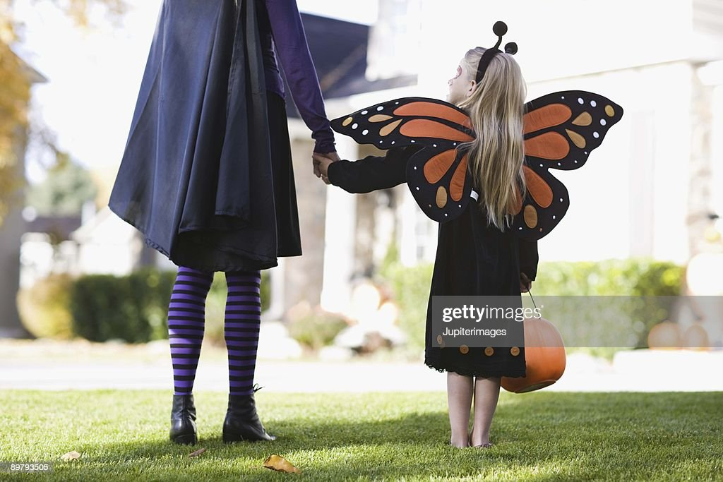 Girl and parent in Halloween costumes : Stock Photo