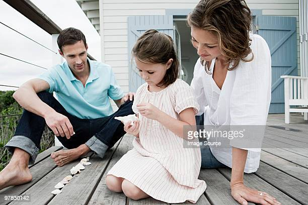 Girl and parents playing with seashells