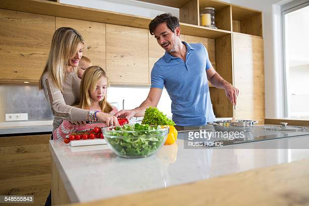 Girl and parents preparing fresh vegetables in kitchen
