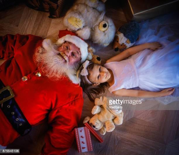 Girl and santa lie on the floor