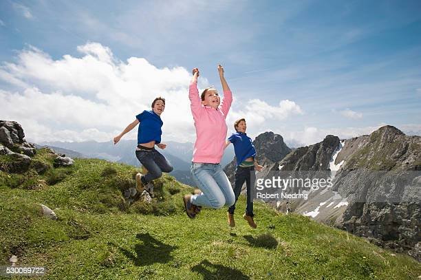 Girl and teenage boys jumping in air Alps