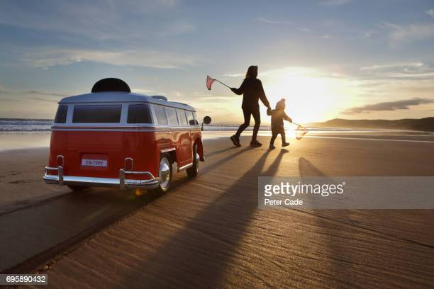 Girl and toddler on beach with toy car and fishing nets