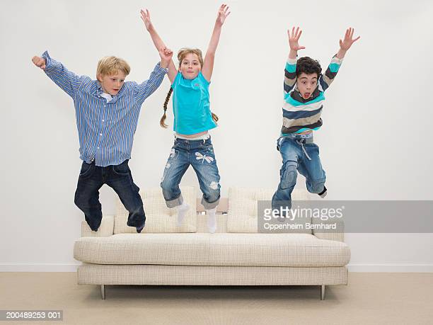 Girl and two boys (8-10) jumping off sofa