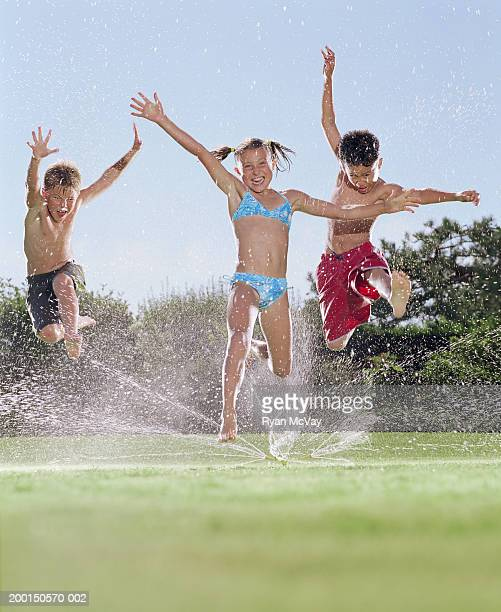 Girl and two boys (8-10) jumping over sprinkler