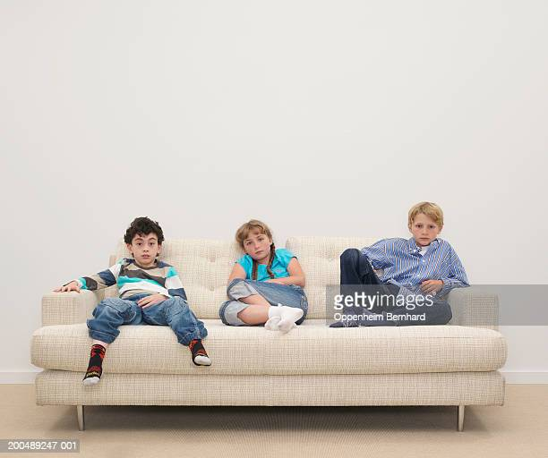 Girl and two boys (8-10) relaxing on sofa