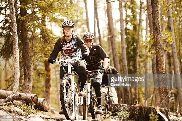 Girl and two guys riding mountain bikes.