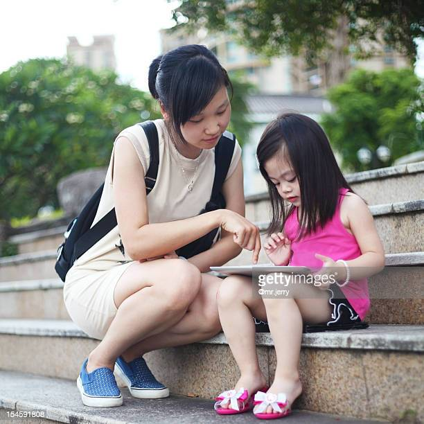 Girl and woman using digital  tablet