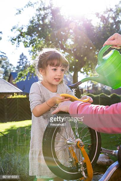 Girl and woman washing bicycle in garden