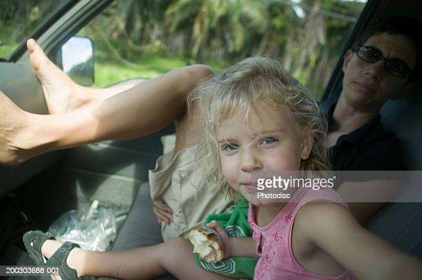 Girl (4-5) and young man sitting in car, portrait