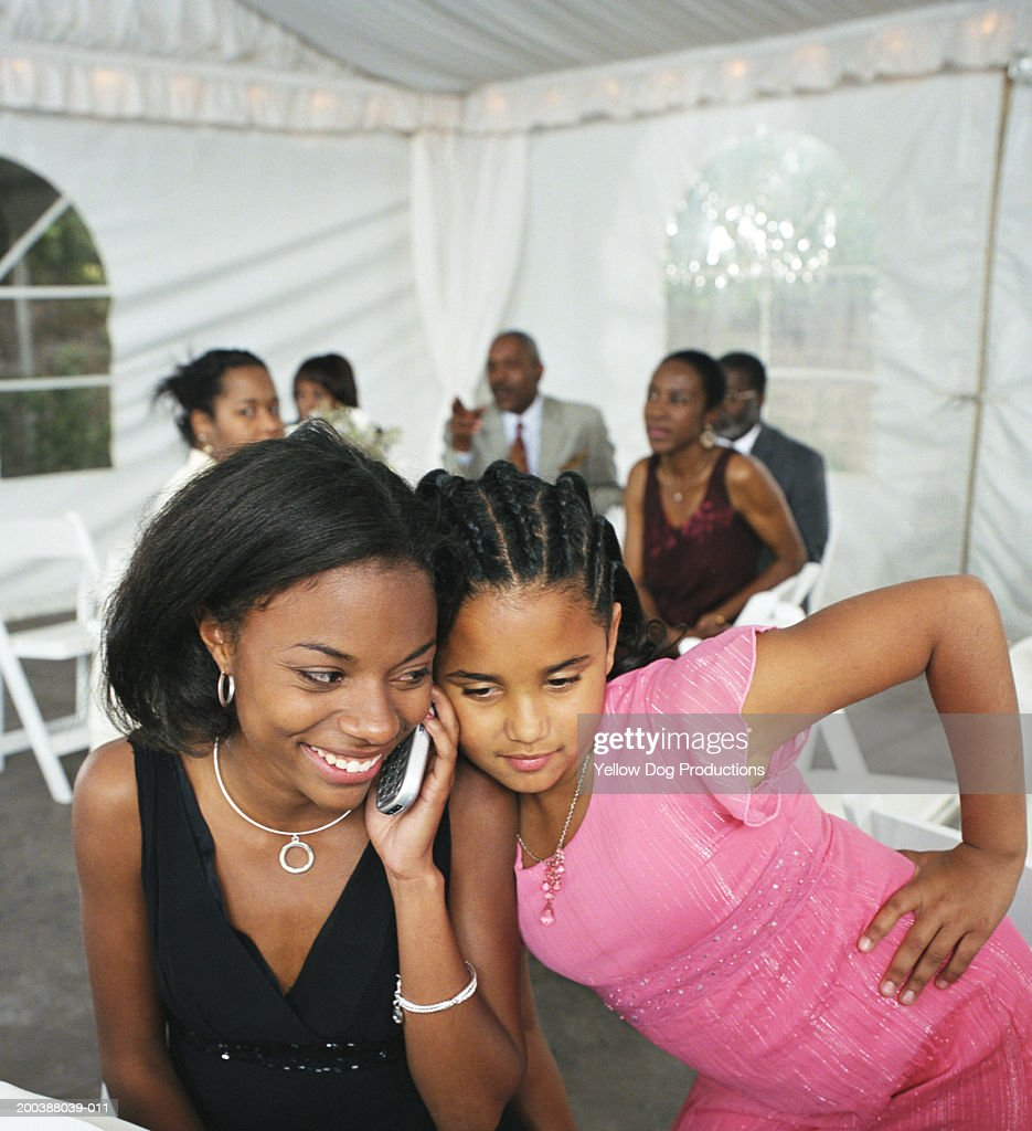 Girl (8-10) and young woman listening to mobile phone at party : Stock Photo