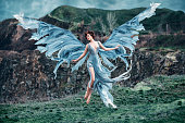 Girl angel with a beautiful wings. As the picture from an old book. Angel flies against the backdrop of the mountains.Fashionable toning, picture in the style of fantasy.