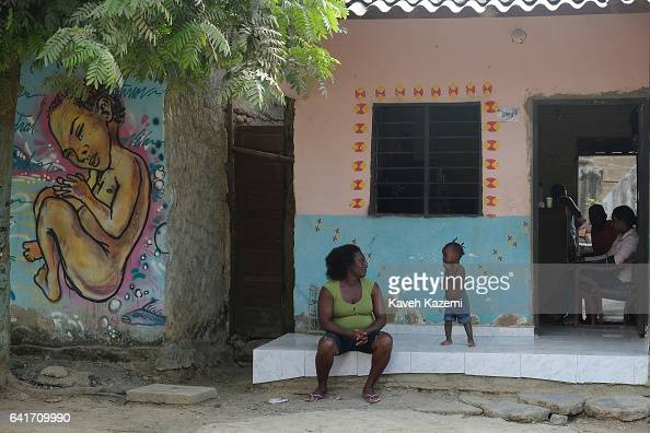 A girl appears with her mother outside a small inhabited home sat next to a mural with writings in SpanishBantú language only spoken by Palenque de...