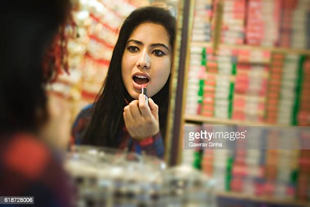 Girl applying lipstick, checking in mirror at cosmetics shop.