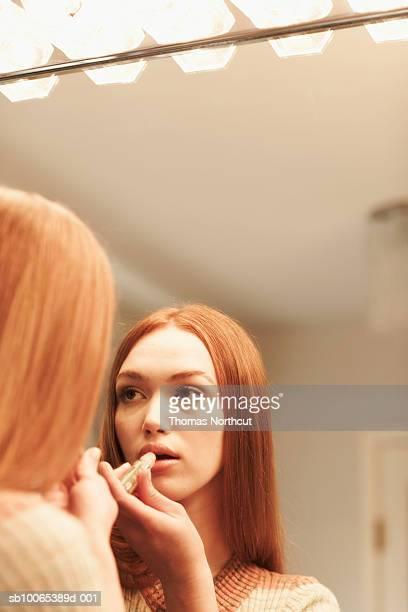 Girl (14-15) applying lipstick, looking in mirror