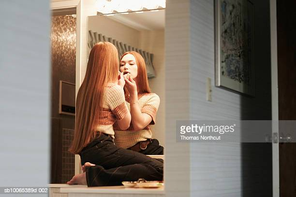 Girl (14-15) applying lipstick, looking in mirror