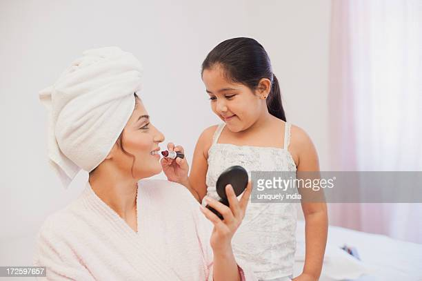 Girl applying lipstick on her mother lips