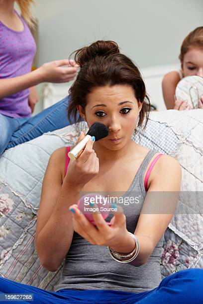 Girl applying makeup in bedroom