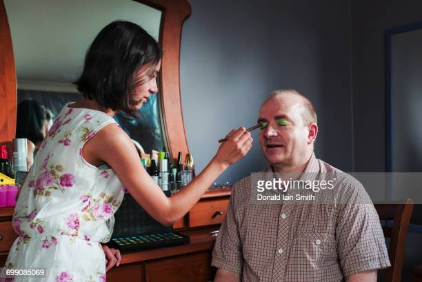 Girl applying makeup to eyes of father